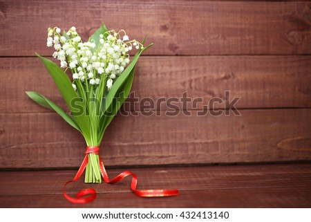 Lily of the valley on wooden background. Lily of the valley bouquet.  Lily of the valley with copy space. - stock photo