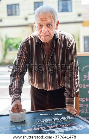 LIMA, PERU - APRIL 12, 2013: An unidentified Peruvian man working in restaurant. Texting cuisine names and prices - stock photo