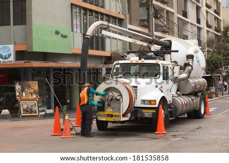 LIMA, PERU - FEBRUARY 11, 2012: Unidentified person of the Concyssa S.A. company cleaning the sewage with the help of a truck on February 11, 2012 in Miraflores, Lima, Peru - stock photo