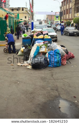 LIMA, PERU - JULY 27, 2013: Pile of garbage waiting to be picked up by the garbage truck at the entrance of the market Mercado No. 2 de Surquillo on July 27, 2013 in Surquillo, Lima, Peru. - stock photo