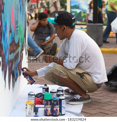 LIMA, PERU - MARCH 3, 2012: Unidentified young man spraying a wall on the Latir Latino, the first Latin-American Street Art Festival on March 3, 2012 in Miraflores, Lima, Peru.  - stock photo