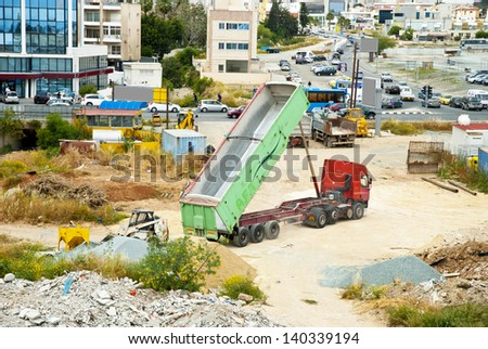 LIMASSOL,CYPRUS-APRIL 15, 2013:Truck unload earth on a construction site in the centre of Limassol,Cyprus on april 15,2013 - stock photo