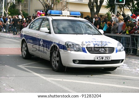 LIMASSOL,CYPRUS-MARCH 6, 2011: Unidentified people and police car in Cyprus carnival parade on March 6, 2011 in Limassol, Cyprus, established in 16th century, influenced by Venetian traditions. - stock photo