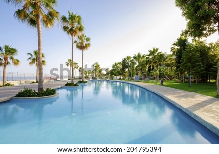 LIMASSOL, CYPRUS - 30 MAY 2014: A view of Molos Promenade on the coast of Limassol city in Cyprus. A view of the walk path surrounded by palm trees, pools of water, grass and the Mediterranean sea. - stock photo