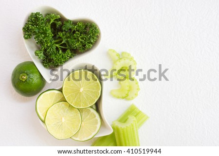 lime and greenery in heart shaped plates with chopped celery stem on white paper. Vegetarian food, detox drink ingredients. Text space background - stock photo