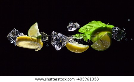 lime and lemon pieces with leaves of peppermint - stock photo
