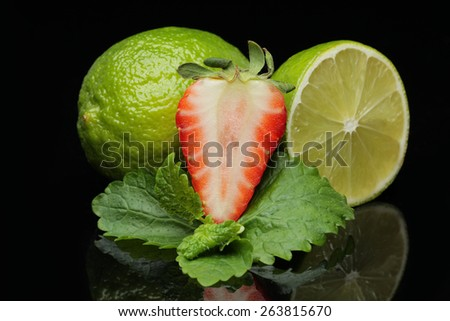 lime and strawberrie isolated on black background - stock photo