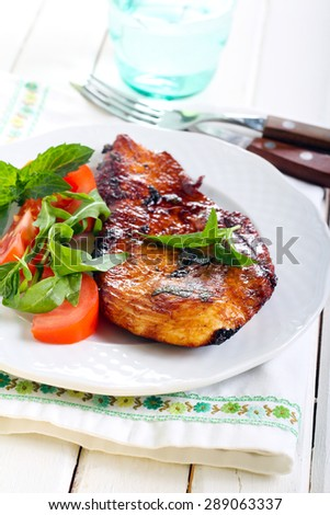 Lime chicken with mint and salad aside on plate