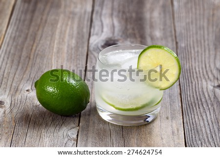 Lime drink, focus on lip of glass and lime slice, with whole lime on rustic wood.  - stock photo