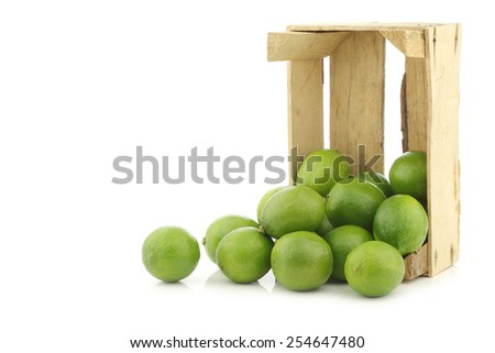 lime fruits in a wooden crate on a white background - stock photo