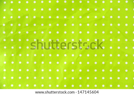 lime green paper with white dots as background - stock photo