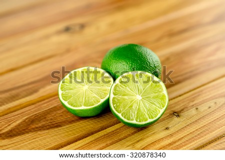 Lime halves on wooden background - stock photo