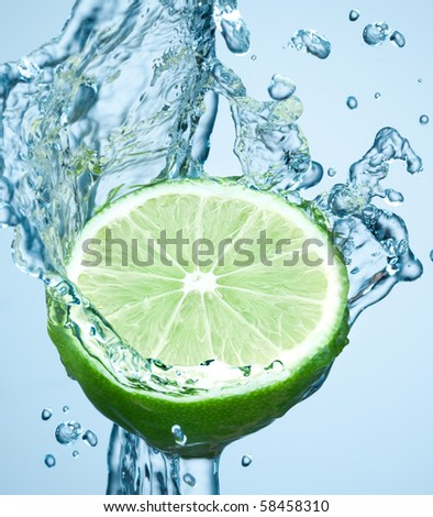lime in spray of water. lime cucumber with splash on background - stock photo