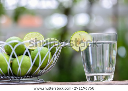Lime in steel basket and glass of lime juice on a wooden table.