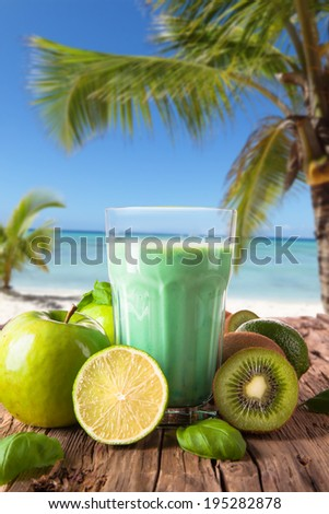 Lime, kiwi and apple slice, mint ice tea on wooden table with tropical beach. Summer concept. Refresh drink.  - stock photo