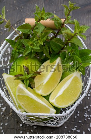 Lime, lime slices and fresh mint in a white vintage basket; fleur de sel on a dark wood surface - stock photo