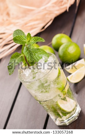 Lime Mojito cocktail with a straw hat on a wooden table, a Cuban cocktail made with cuban rum, lime, sugar and a splash of soda - stock photo