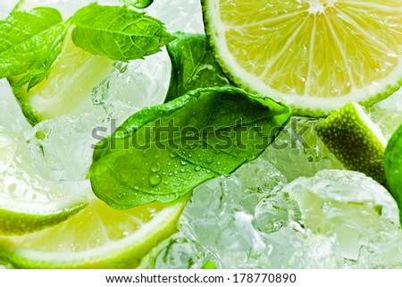 lime pieces and leaves of mint with ice - stock photo