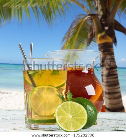 Lime, slice, mint ice tea on wooden table with tropical beach. Summer concept. Refresh drink.  - stock photo