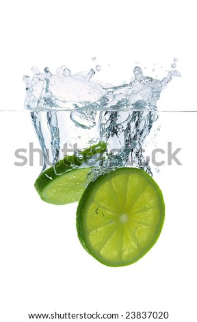 Lime slices falling into the water - stock photo