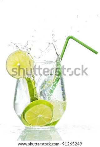 Lime splashing into glass of water on white background - stock photo