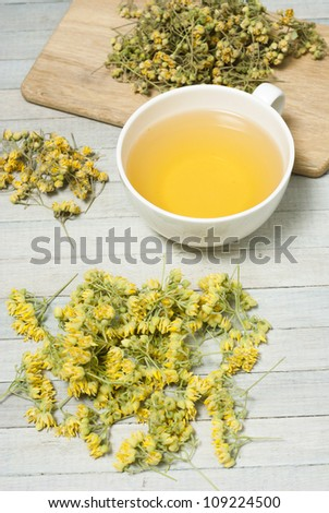 lime tree tea, blossoms, herbal tea on white wooden