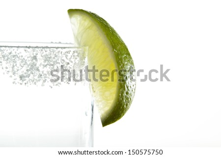 lime wedge and salt on the rim of a glass isolated on a white background - stock photo