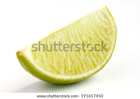 Lime wedges arranged on a white surface. Selective focus. - stock photo
