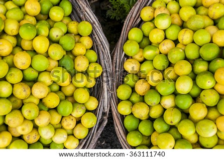 Limes an lemons in two baskets at asian market - stock photo