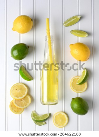 Limes and Lemons surrounding a bottle of soda on a white bead board table. High angle shot in vertical format. - stock photo