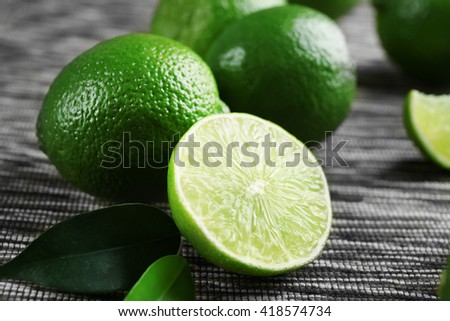 Limes and slices on wooden table, closeup - stock photo