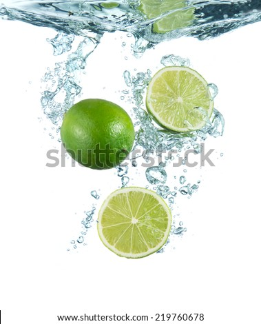 limes splashing into the water - stock photo