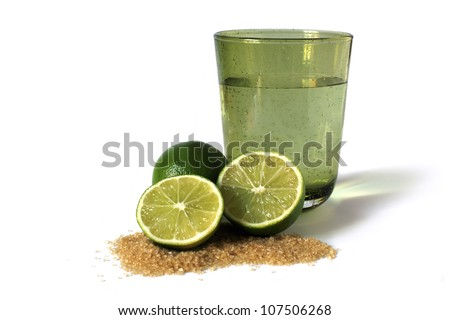 limes, sugar cane and green glass with water - stock photo