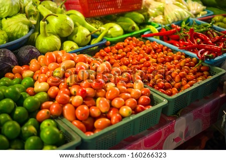Limes, tomatoes, peppers on city market in asia