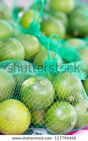 Limes with green plastic net for sell in market. - stock photo