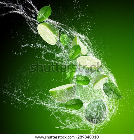 Limes with water splash isolated on dark background - stock photo