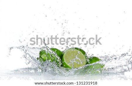 Limes with water splash isolated on white - stock photo
