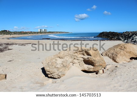 Limestone blocks on the rocky sandy groyne at the Cut into the Indian ocean at Port Bouvard western Australia in mid winter.