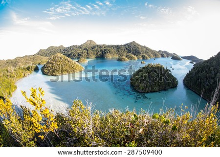 Limestone islands surround a beautiful tropical lagoon in Raja Ampat, Indonesia. This remote area harbors some of the Coral Triangle's most healthy marine habitats. - stock photo