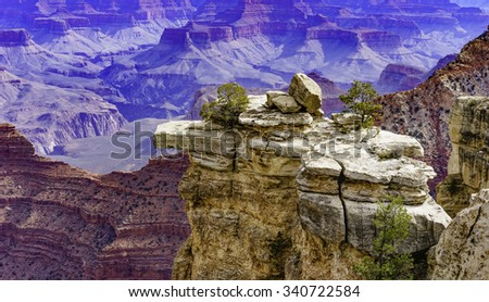 Limestone promontory with deep cracks, dangerous ledges, and a teetering boulder or two, with vast plateaus and eroded cliffs in the distant background, along South Rim of Grand Canyon in March - stock photo