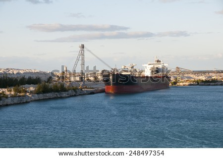 Limestone Ship riding high in the water waiting to be filled by converyors near sunset - stock photo