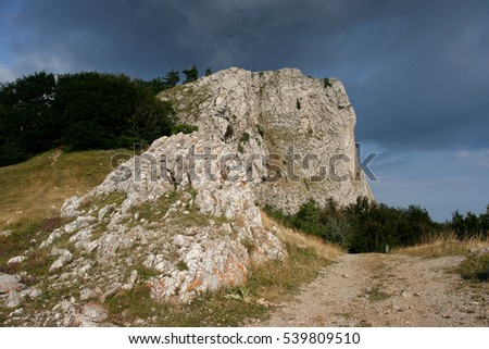 Limestone sunlit cliffs the small path among the grass in Crimean mountains in summer.