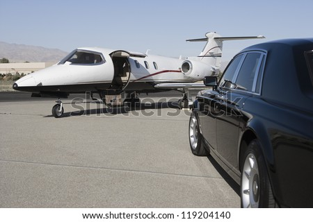 Limousine and private jet on landing strip - stock photo