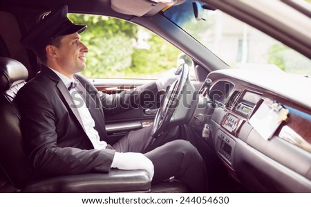 Limousine driver driving and smiling in his limousine - stock photo