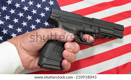 Limp man's hand holding automatic pistol against US flag.