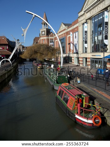 Lincoln, UK,  23 February 2015. Looking up the River Till towards 'Stokes' coffee house with multi-coloured narrow boats moored alongside the quay and a shopping precinct. Clock tower against blue sky - stock photo