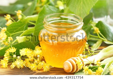 Linden honey in glass jar and linden flowers - stock photo