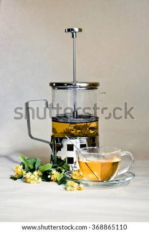 Linden tea brewed in the press with a teacup. Linden flowers and leafs - stock photo