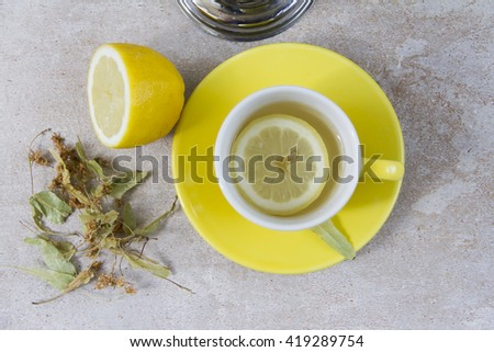Linden tea in yellow cup. Beige background. Five o'clock, tea time.  - stock photo