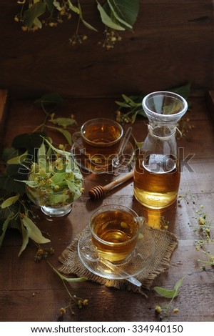 Linden tea with honey and bowl with linden flowers on wooden background in sunshine light - stock photo